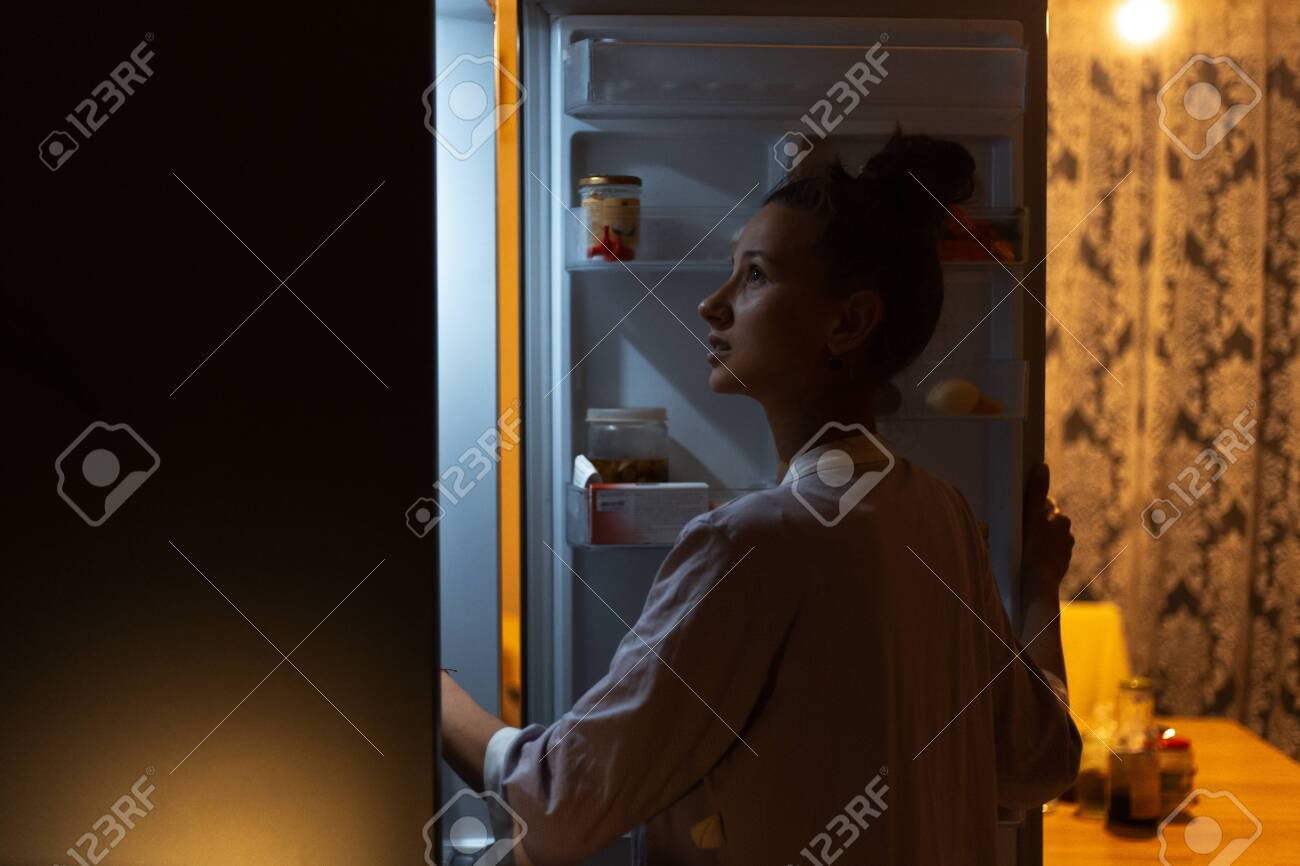 Young girl looking in fridge at night. - 141229369
