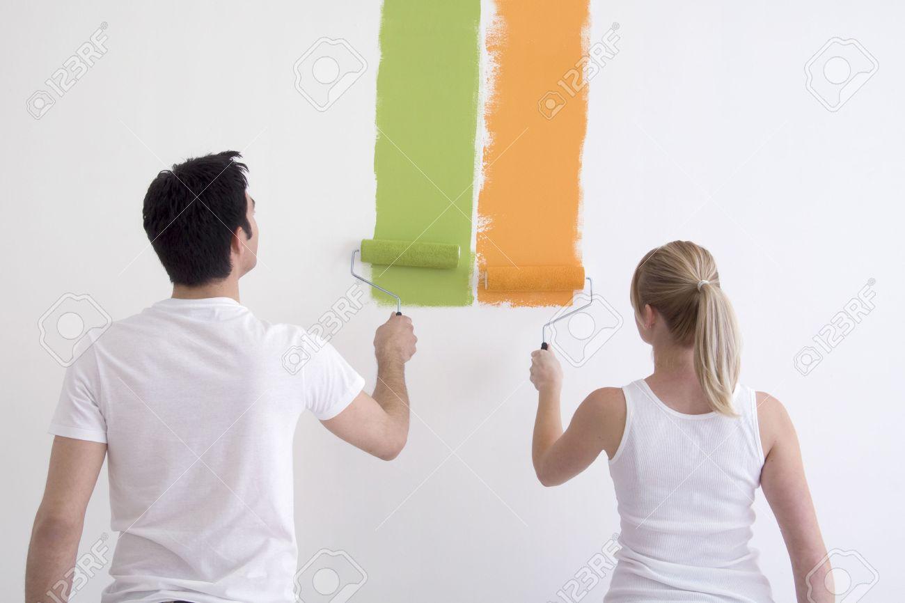 Man en vrouw schilderen van kleuren op een witte muur. hun rug ...