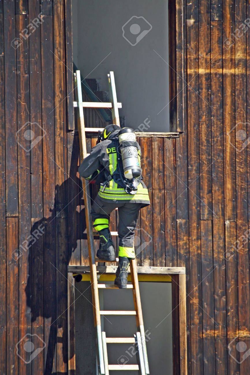 italian firefighter oxygen cylinder to peg up the ladder stock photo italian firefighter oxygen cylinder to peg up the ladder to extinguish a dangerous fire