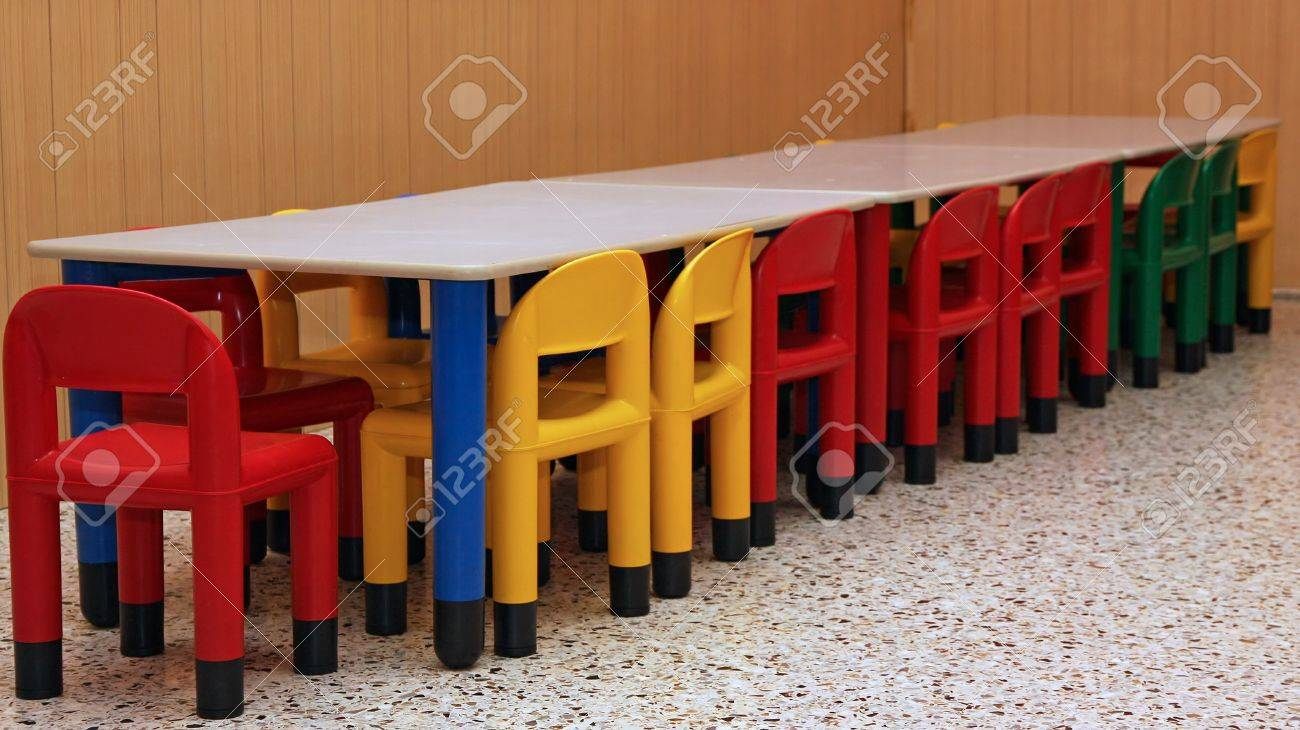 colored plastic chairs and a table in the refectory of the preschool