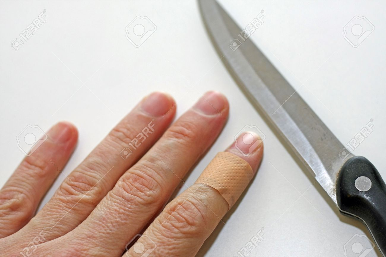 hand with finger with a band aid and the sharp blade of the knife in the kitchen Stock Photo - 17590256