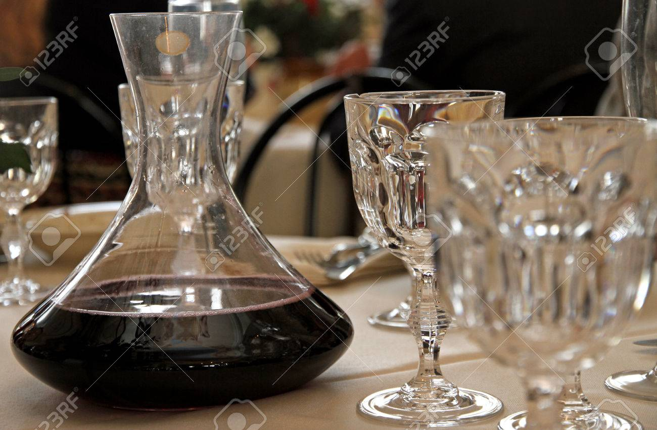 Carafe Decanter With Red Wine In A Table With Many Glass Of Fine Bohemian  Glassware Stock