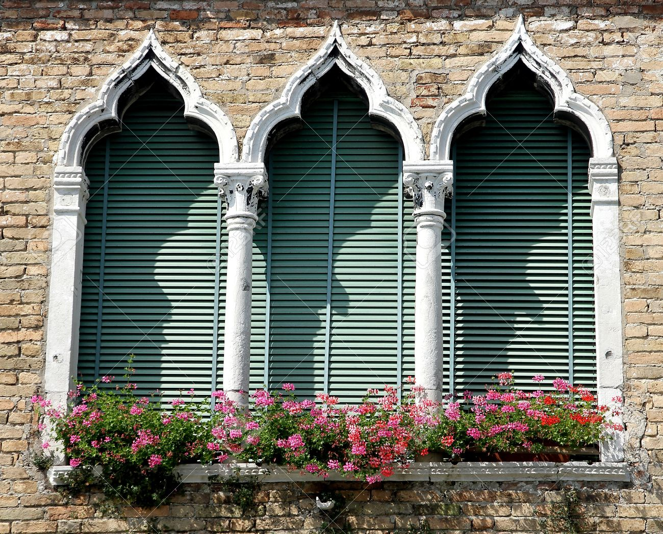 flowery balcony in Venetian style with arched windows of a historic  residence in Venice Stock Photo