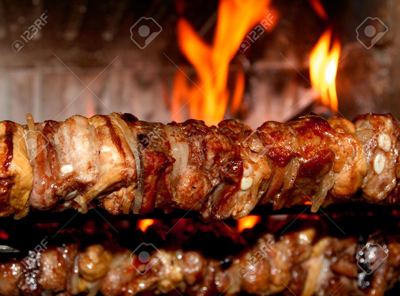 spit roast with of tasty meat cooked on a spit in the fireplace Stock Photo - 30389421