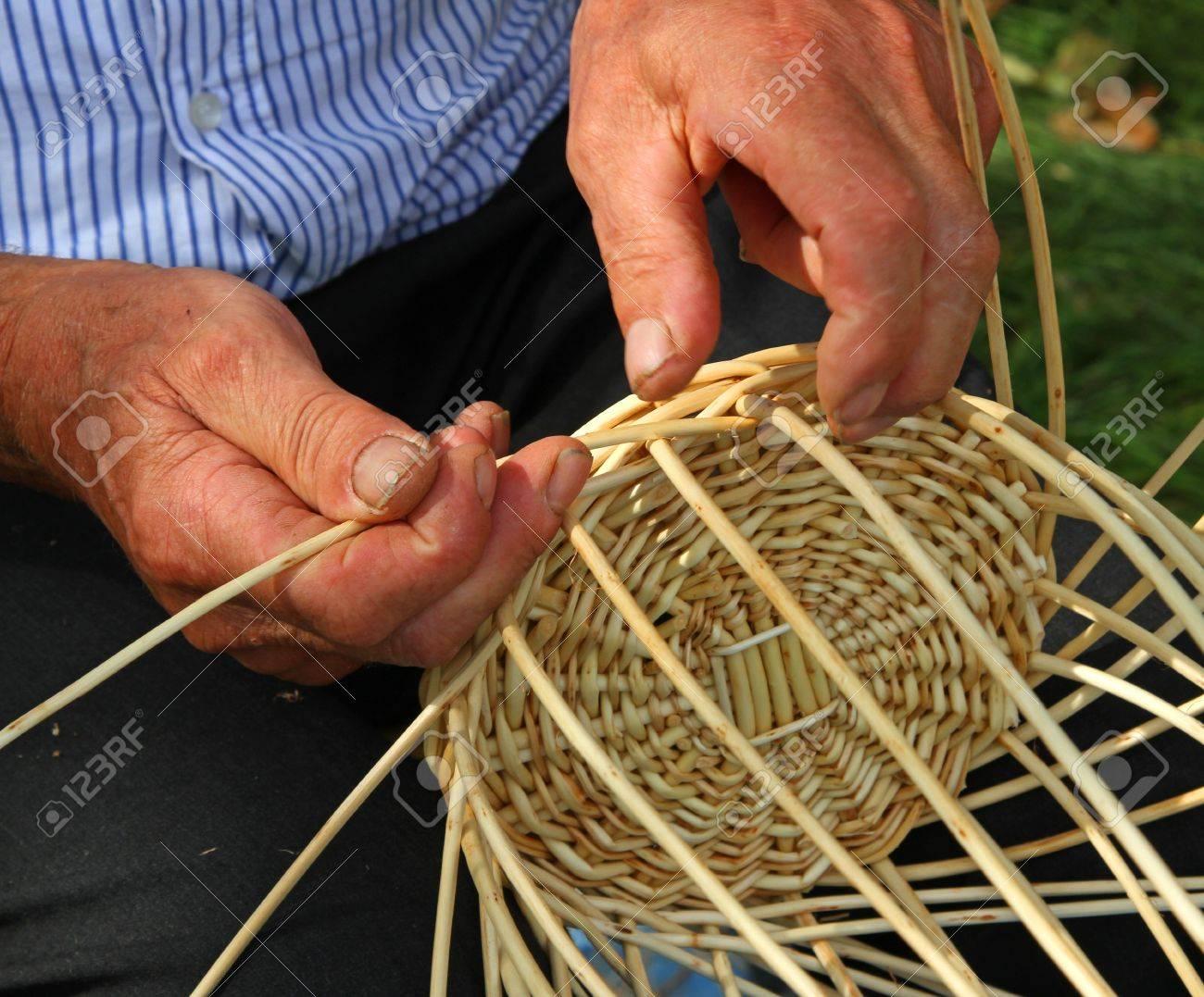 manos de personas mayores que trabajan la caa para hacer una cesta de mimbre foto de