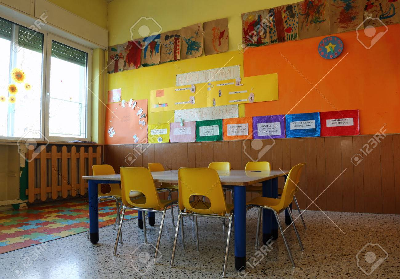 Kindergarten classroom table - Kindergarten Classroom With Yellow Chairs And Table With Drawings Of Children Hanging On The Walls Stock