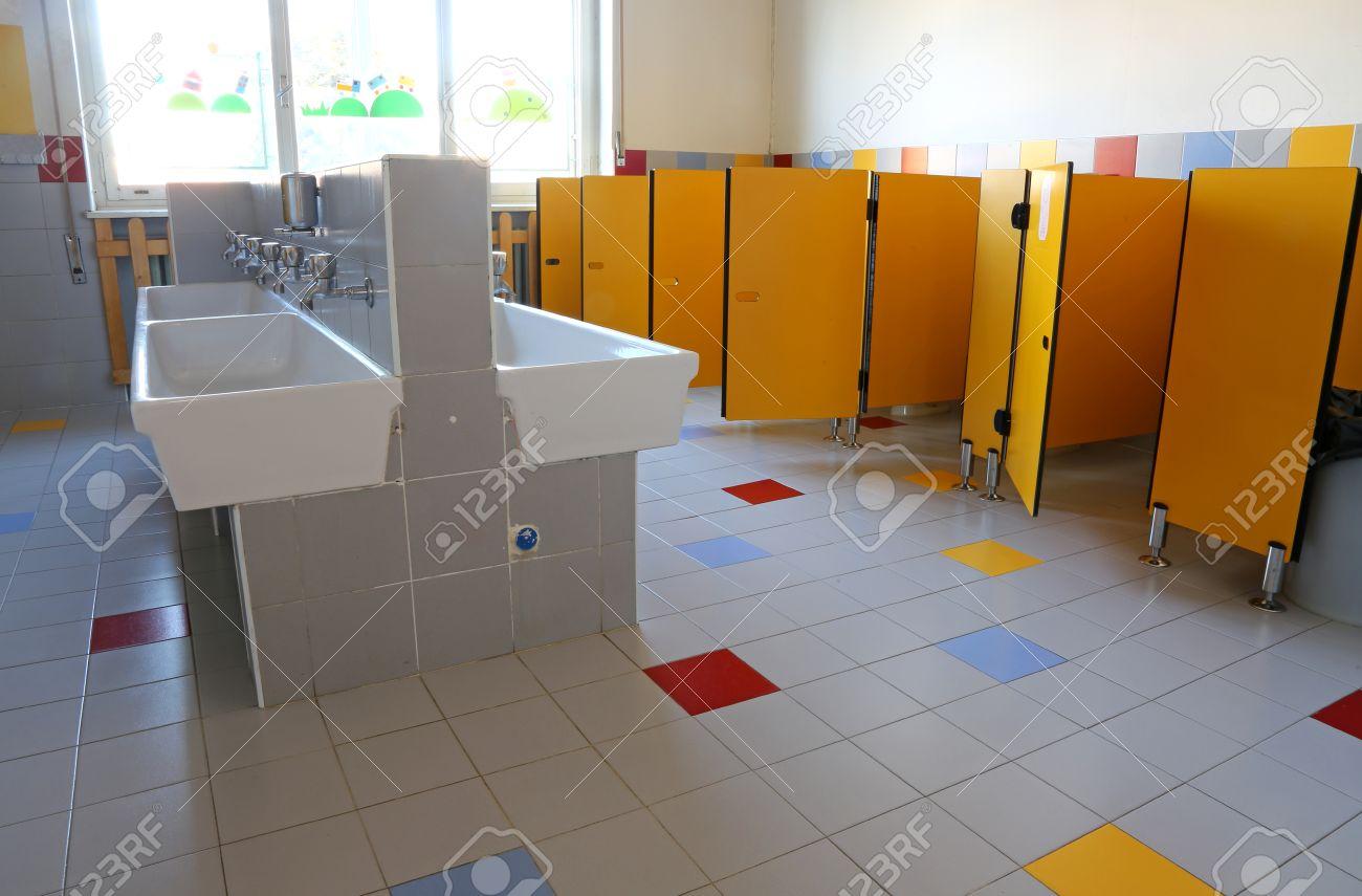En el interior del cuarto de baño de la escuela infantil con sumideros  blancas y puertas amarillas