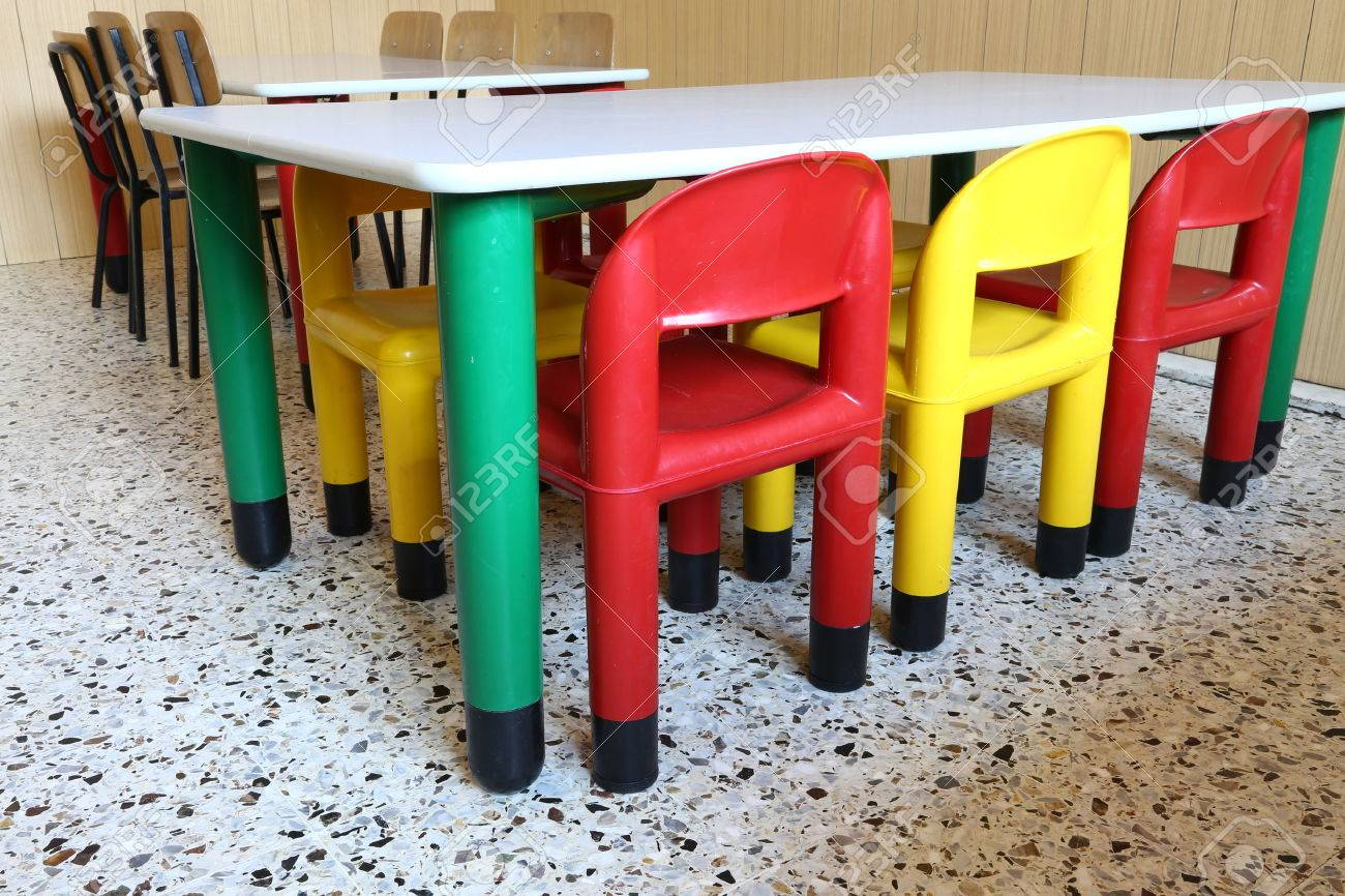 colored plastic chairs and small tables in the nursery class stock