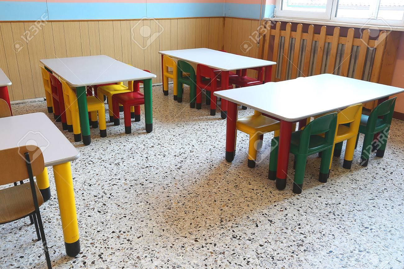 Sillas de plástico de colores y pequeñas mesas de comedor escolar para los  niños