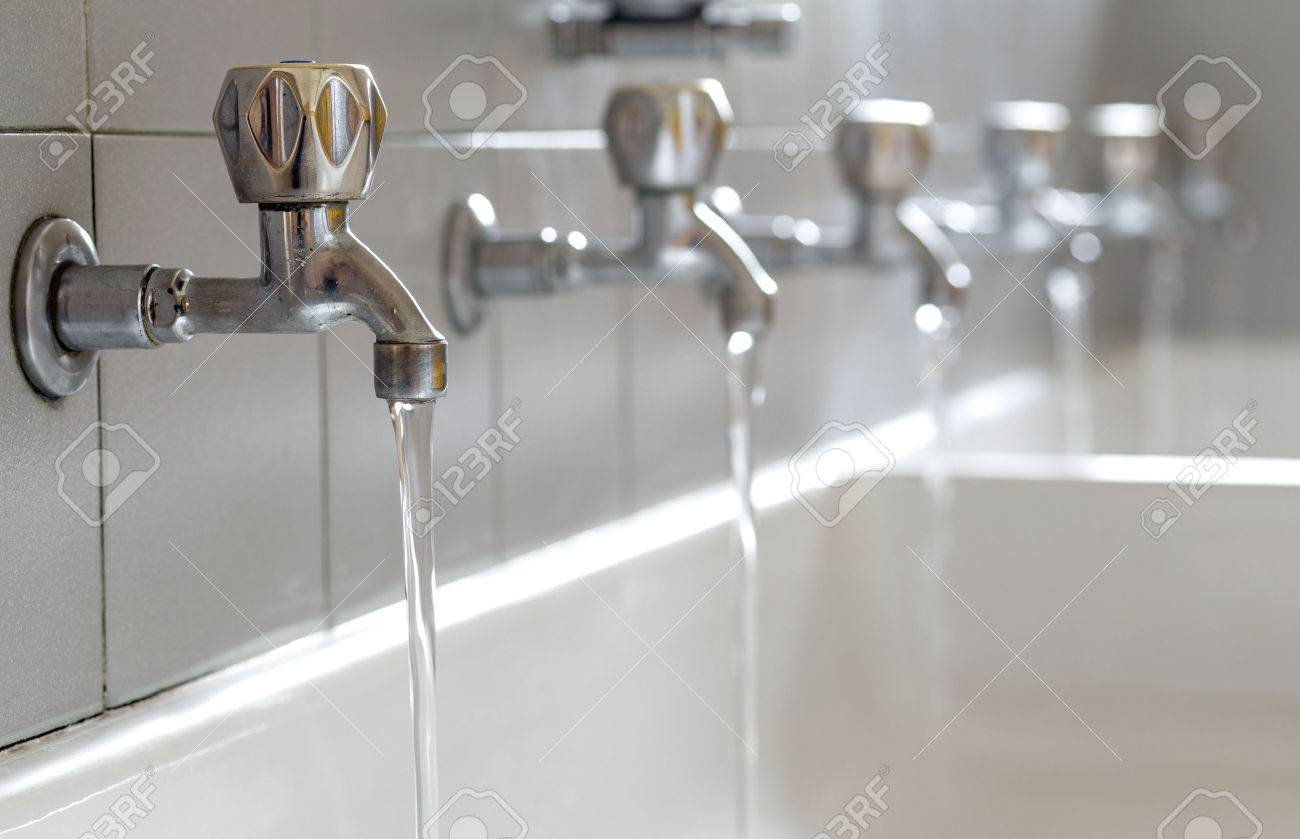 Many steel taps with drinking water flowing in college bathroom Stock Photo - 39552858