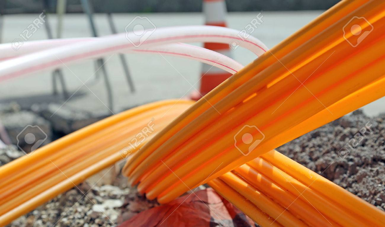 Orange pipes for fiber optics in a large city road construction to connect high speed internet Stock Photo - 43389961