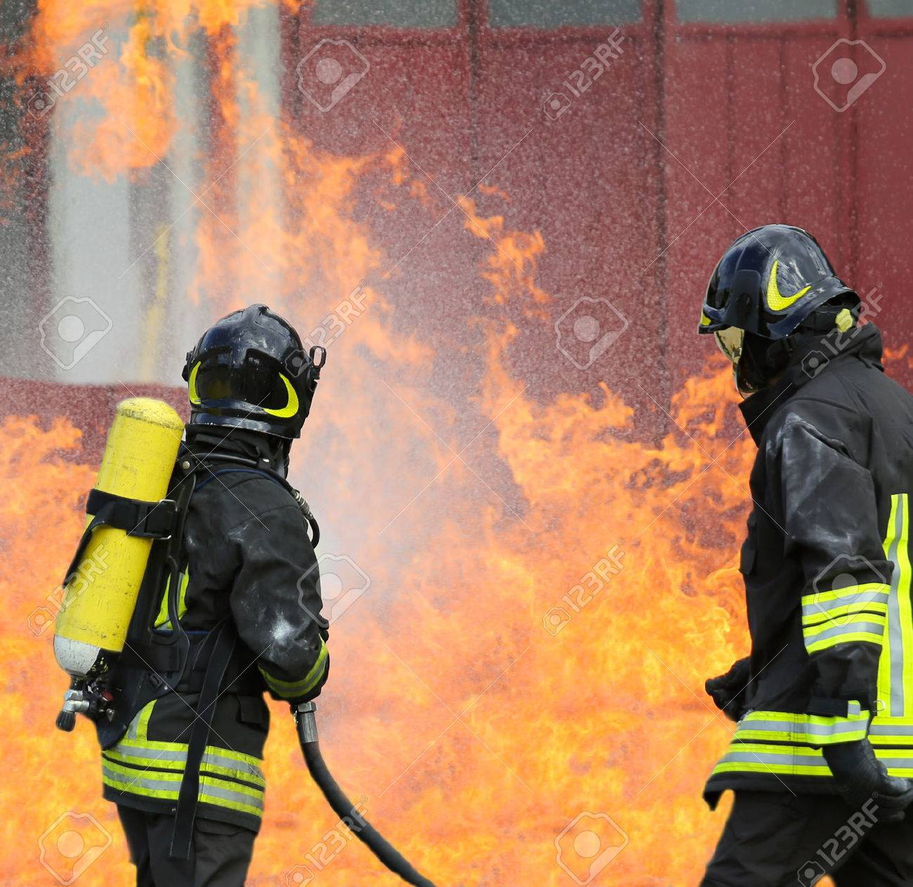 firefighters with oxygen bottles off the fire during a training exercise in Firehouse Stock Photo - 45525189