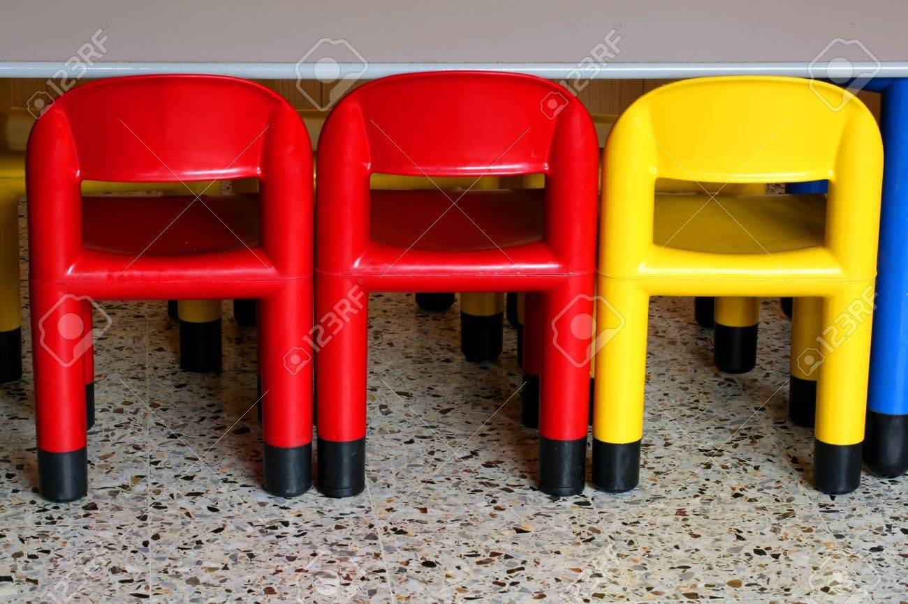 three colored plastic chairs in a nursery for small children stock