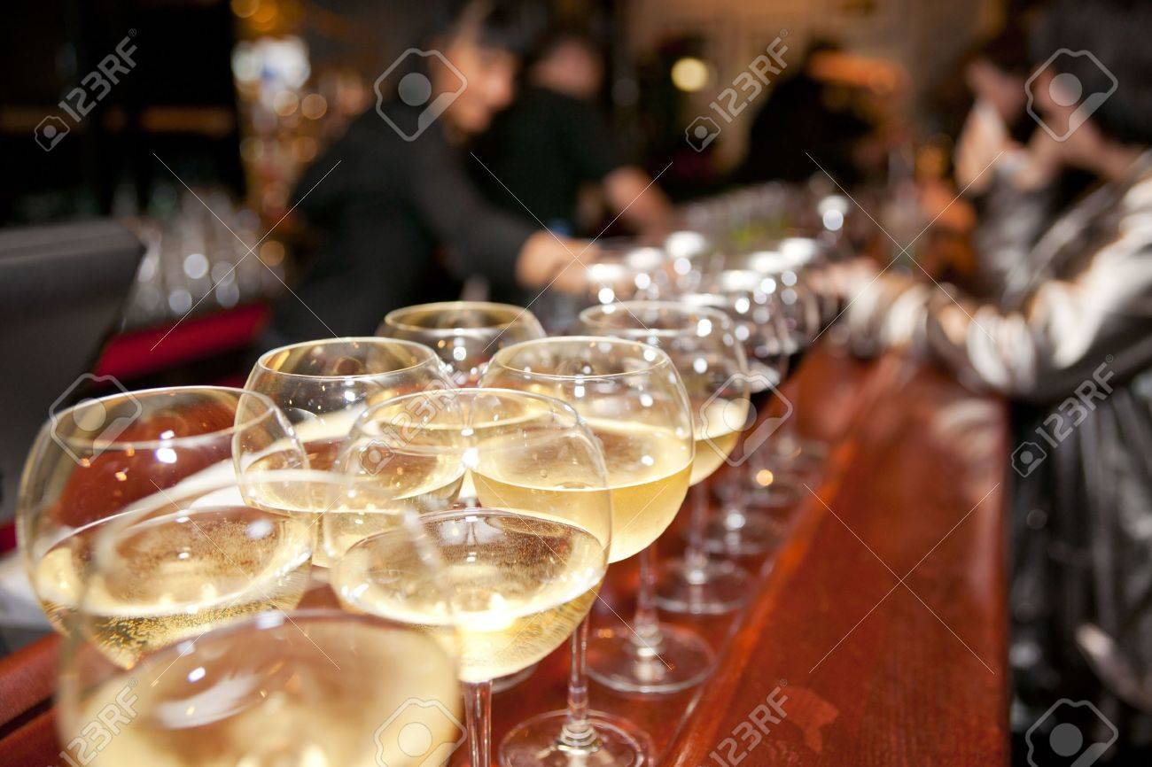Wineglasses on bar counter with blurred crowd in background Stock Photo - 5113644