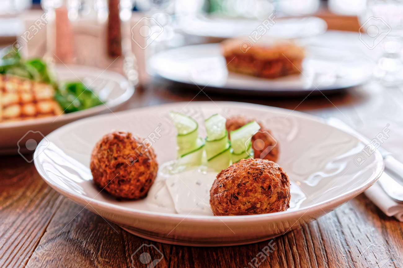 Zucchini croquettes and other dishes on restaurant table, Greek food, toned - 150808121