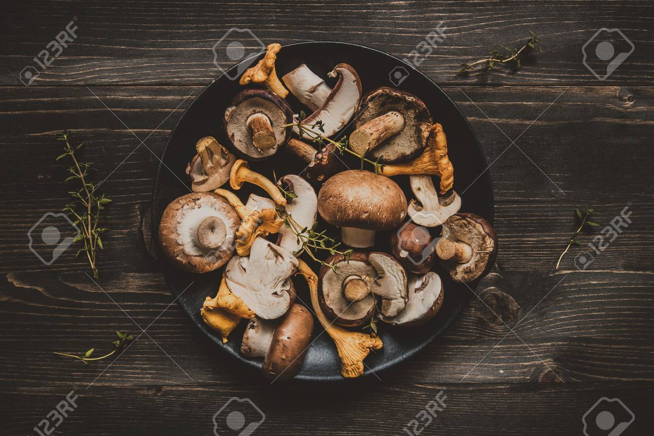 Fresh mixed forest mushrooms on the wooden black table, top view. Stock Photo - 86891244