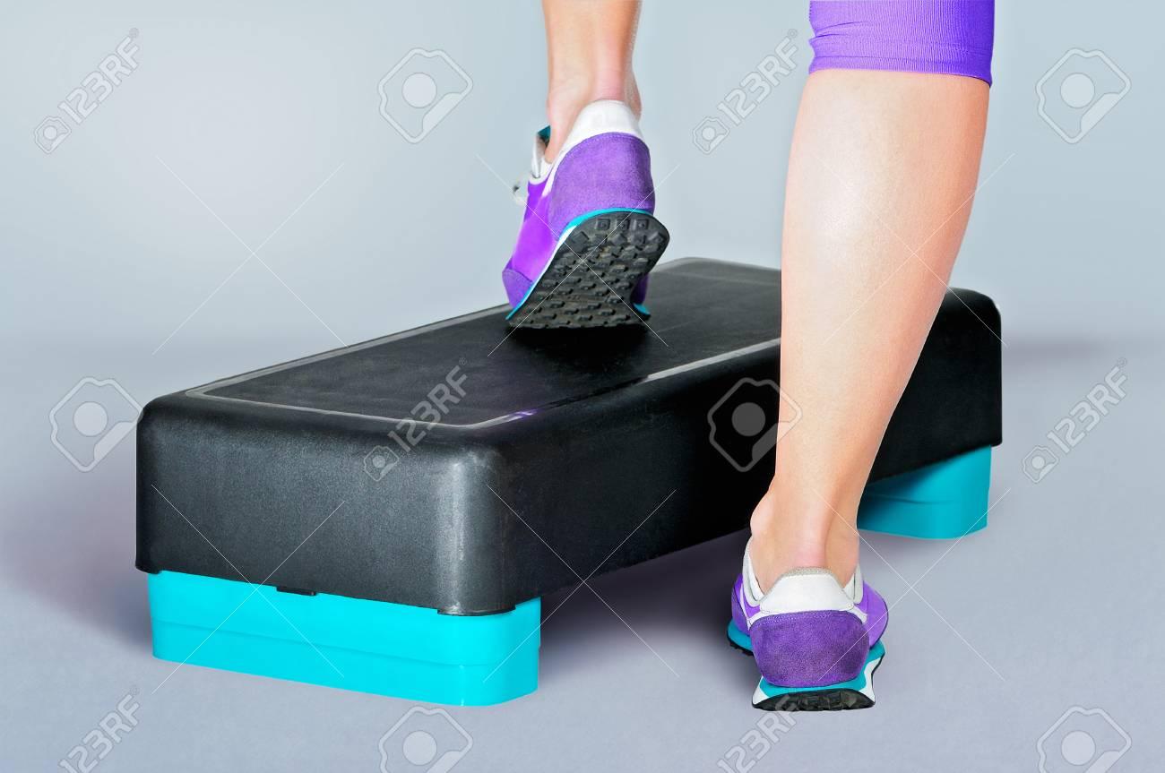 size 40 75ead 1a13d Piedi femminili in scarpe da ginnastica viola fanno esercizio su un  nero-turchese aerobica idoneità passo. Vista posteriore.