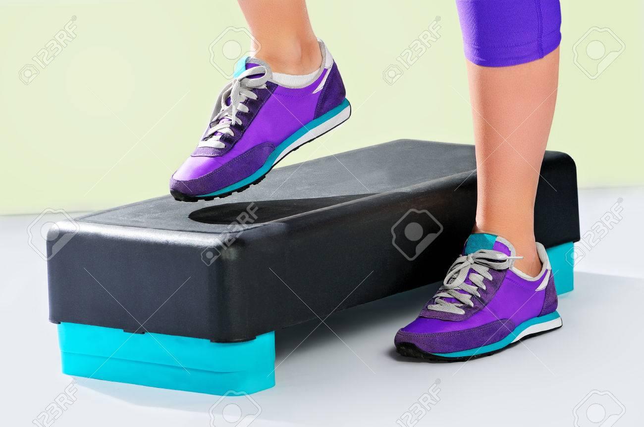 pretty nice a263a 9a5e1 Piedi femminili in scarpe da ginnastica viola fanno esercizio su un  nero-turchese aerobica idoneità passo. Vista laterale.