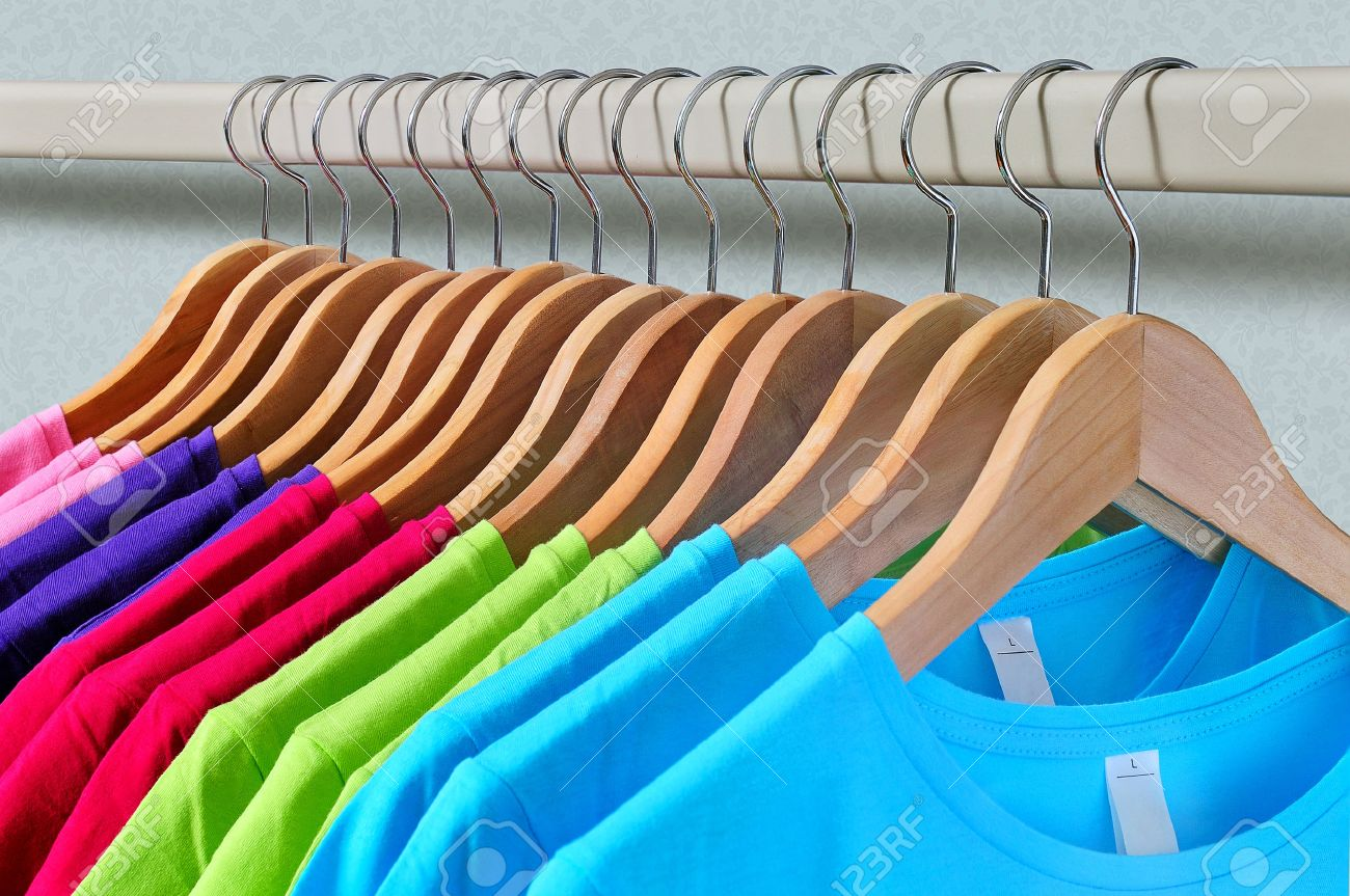 Pink, purple, crimson, bright green and turquoise women's T-shirts hanging on wooden hangers on gray background Standard-Bild - 39363398