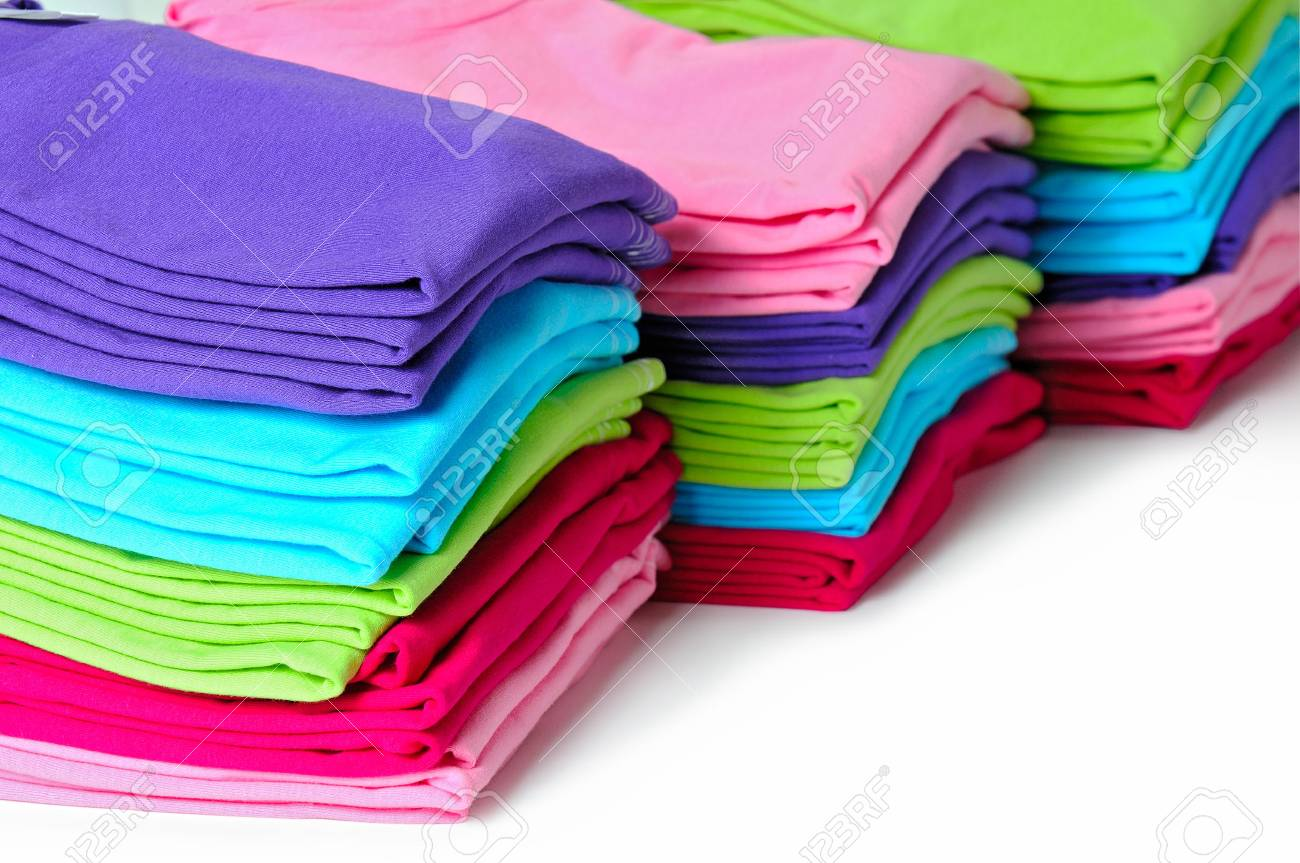 Pink, purple, crimson, bright green and turquoise women's T-shirts lie piles on a white background. Standard-Bild - 39363400