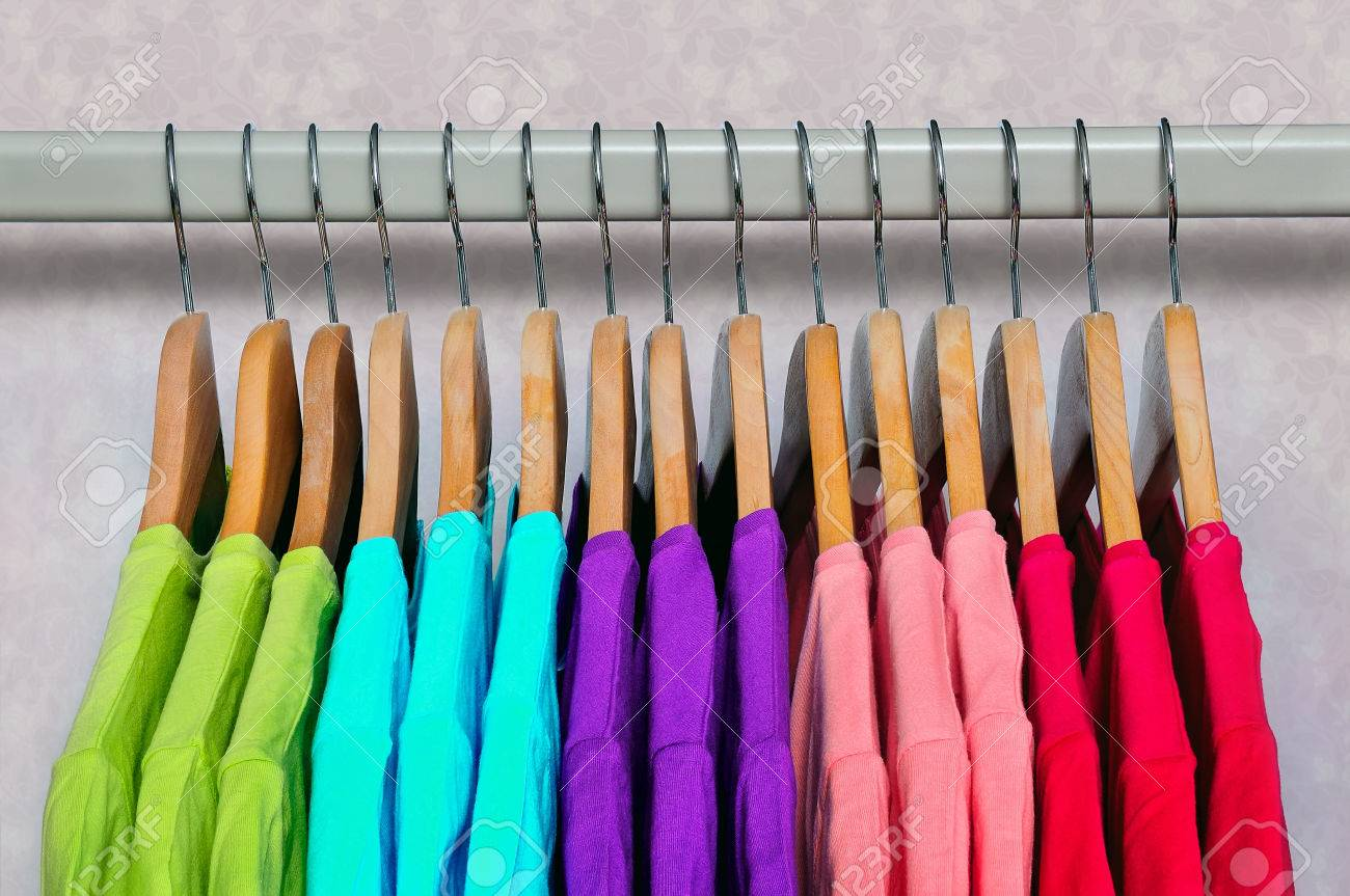 Pink, purple, crimson, bright green and turquoise women's T-shirts hanging on wooden hangers on light background. Side view. Standard-Bild - 46965005