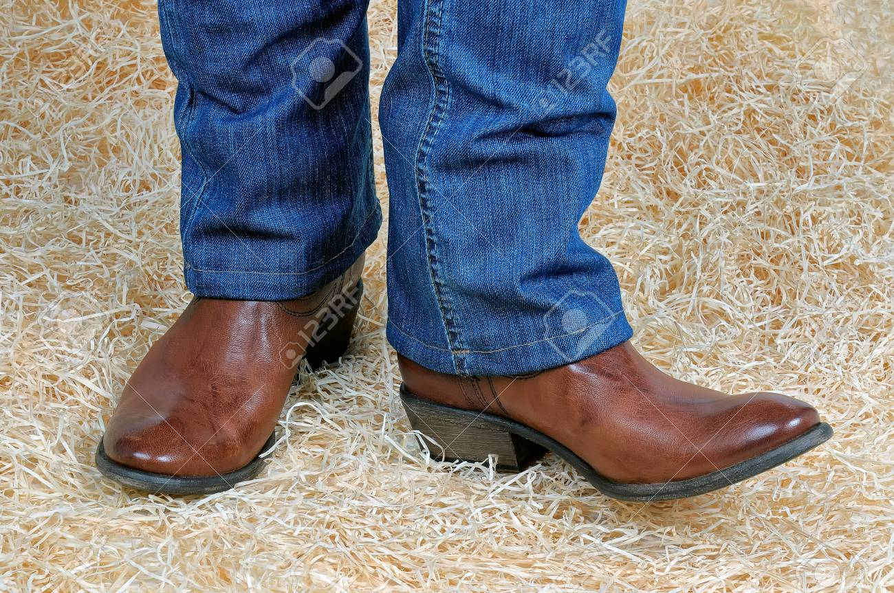 e8357b7a376 Pair of legs in traditional vintage brown cowboy boots and blue..
