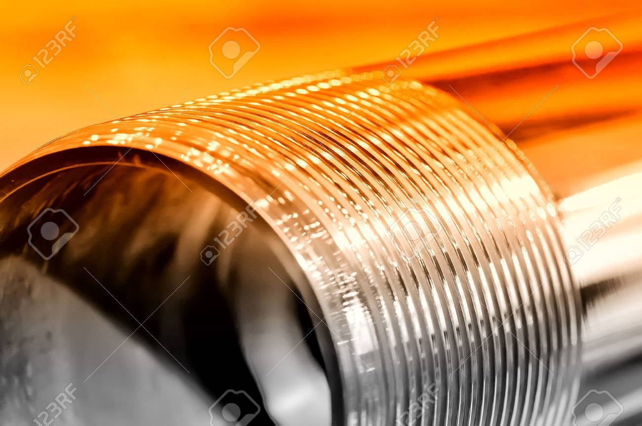 Steel rod with a screw thread. Red toning. Small depth of field. Close up Standard-Bild - 85275046