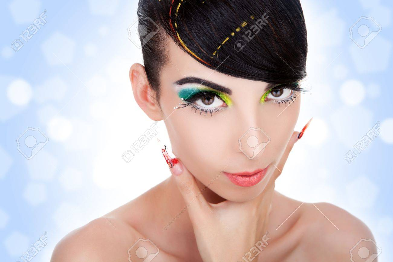 Portrait of beautiful woman with creative strong eyebrows makeup, clean skin, cheekbones and fancy manicure on bright blue background. Fashion style, manicure, cosmetics and make-up. Stock Photo - 11971734