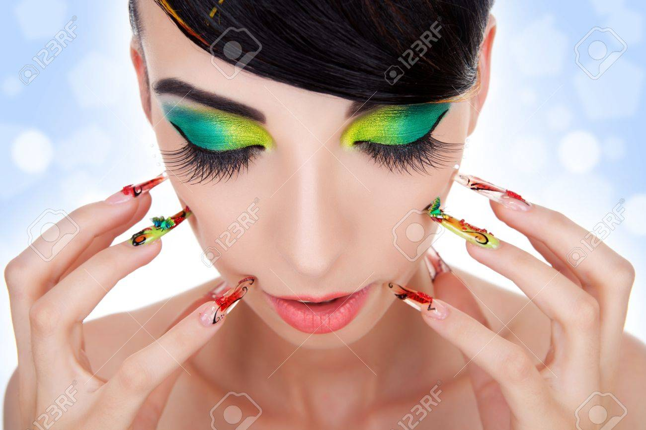 Beautiful model with long fingernails against face and looking down. Luxury fashion style, manicure, cosmetics and make-up. Close-up portrait of female model with red lipstick, fingernails and clean skin Stock Photo - 11971752