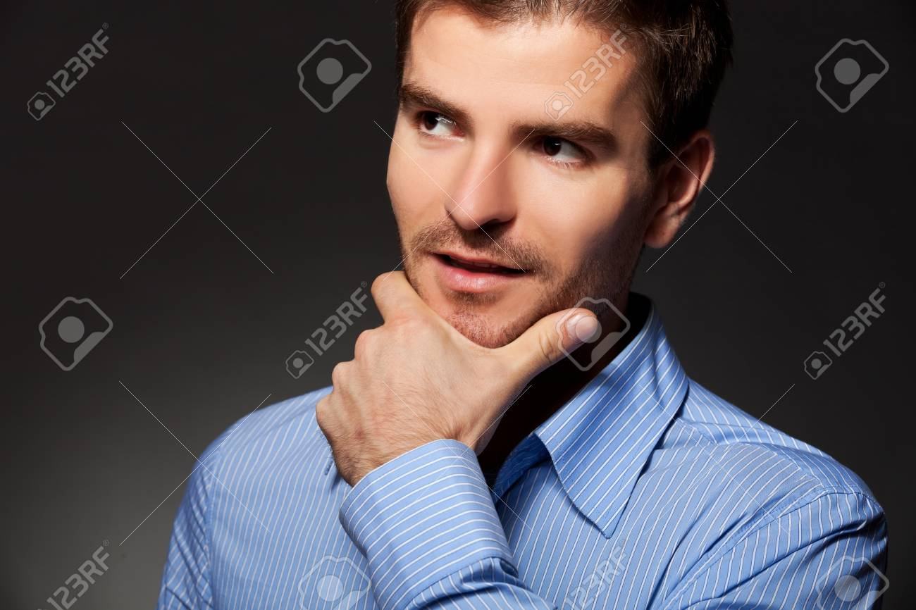 closeup portrait of young business man thinking on a gray background Stock Photo - 12076962