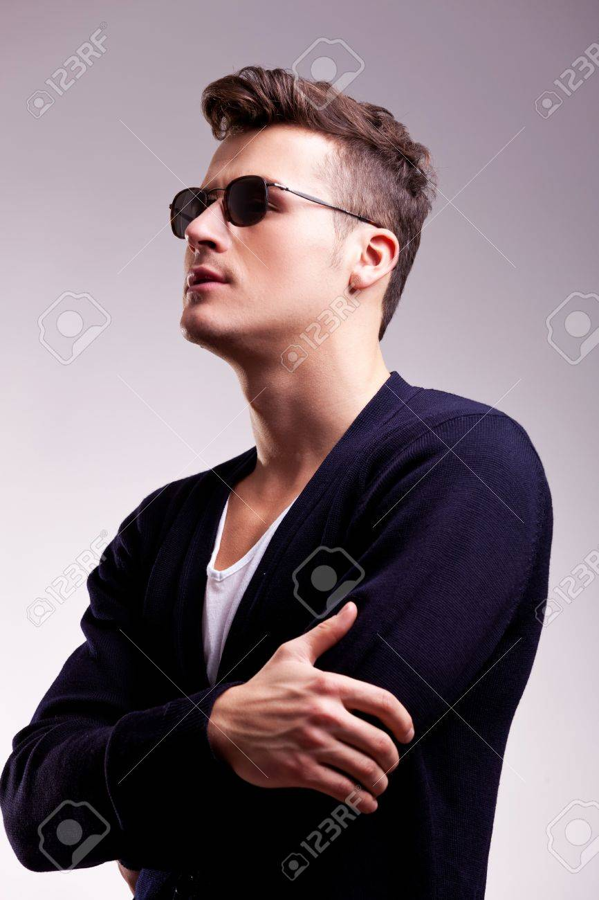 side of a handsome young male model wearing sunglasses and a casual sweater on a gray background Stock Photo - 12582195