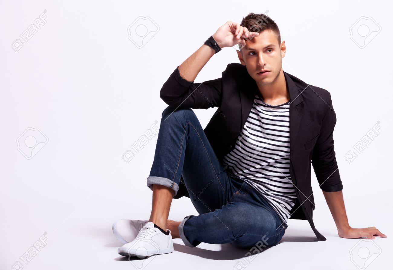 deb8aa53d9a Banque d images - La mode jeune homme décontracté à la recherche de quelque  chose à ses côtés alors qu il était assis sur fond gris