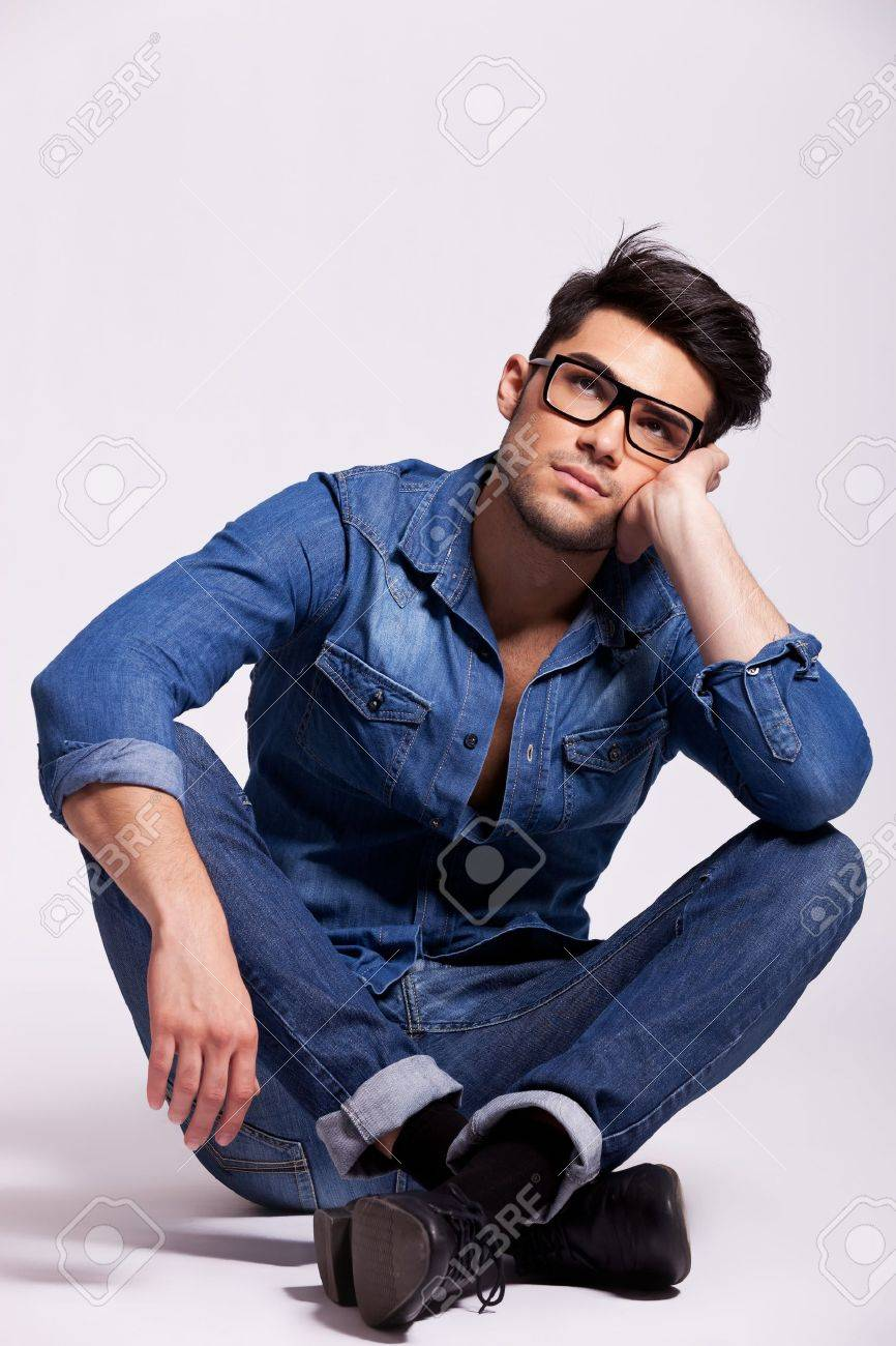 attractive young fashion man wearing glasses, sitting and thinking on a gray studio background Stock Photo - 15154773