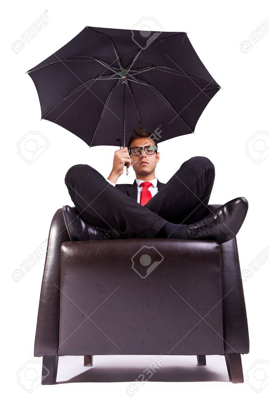 Image of a business man sitting in comfortable armchair with an umbrella in his hand Stock Photo - 15500279