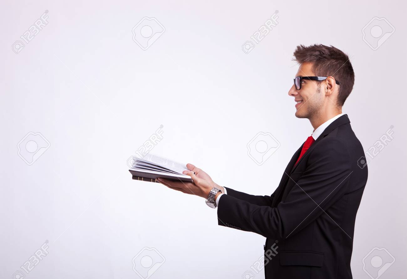 side view of a student looking at something imaginary comming out of his book Stock Photo - 15500431