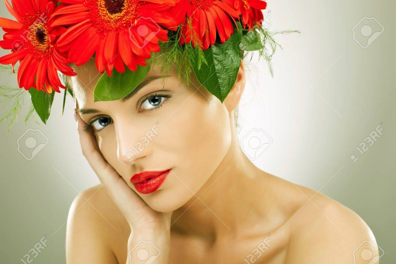 gorgeous seductive woman wearing flowers in her hair holding her head in her palm Stock Photo - 15500186