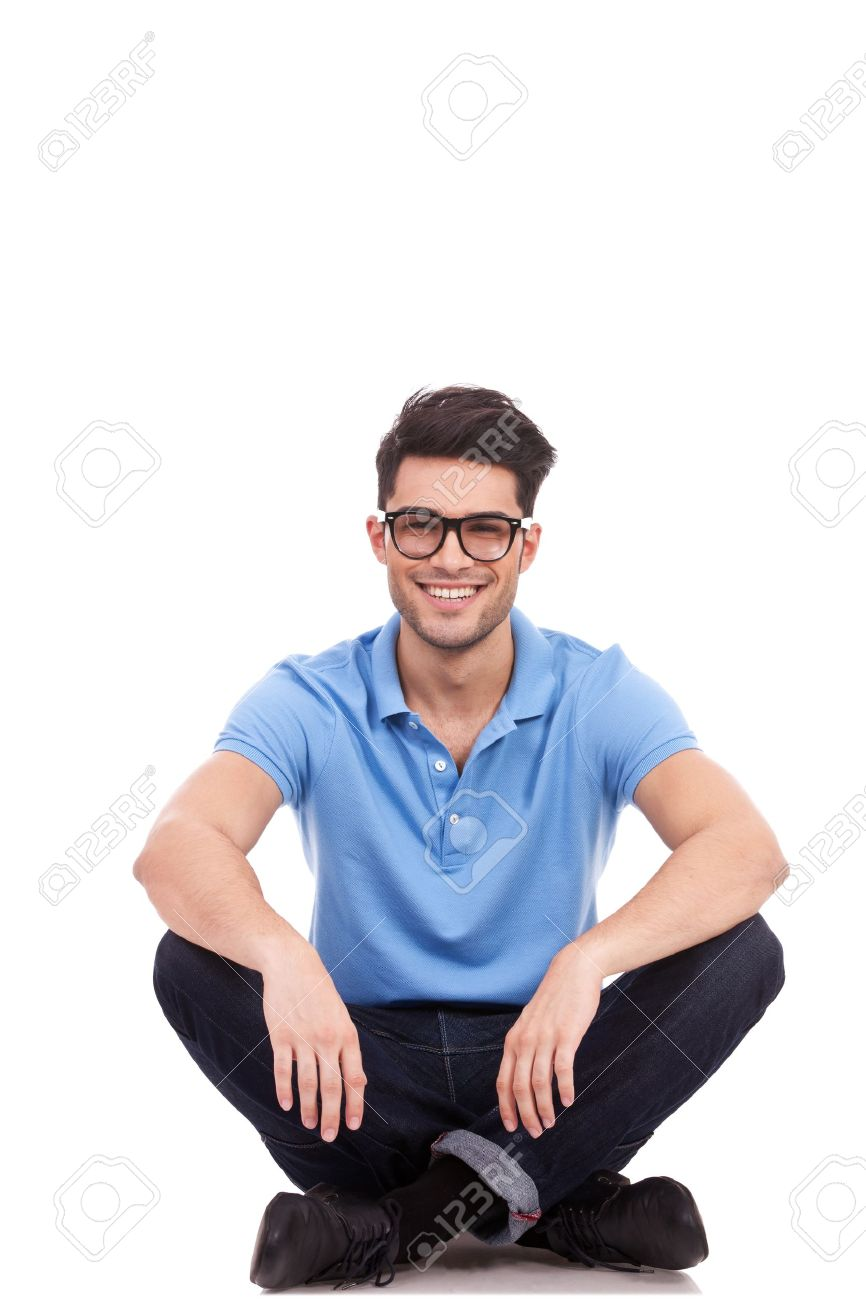 young casual man with eyeglasses sitting on the floor in the lotus position and smiling Stock Photo - 15618143
