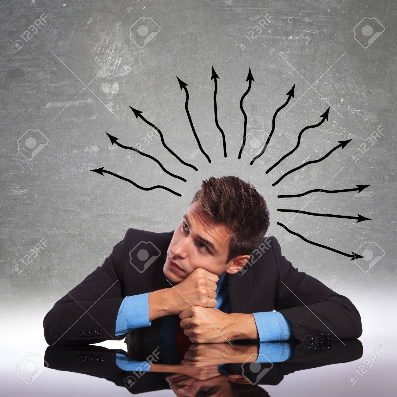 confused business man sitting at his desk and looking away Stock Photo - 17624939
