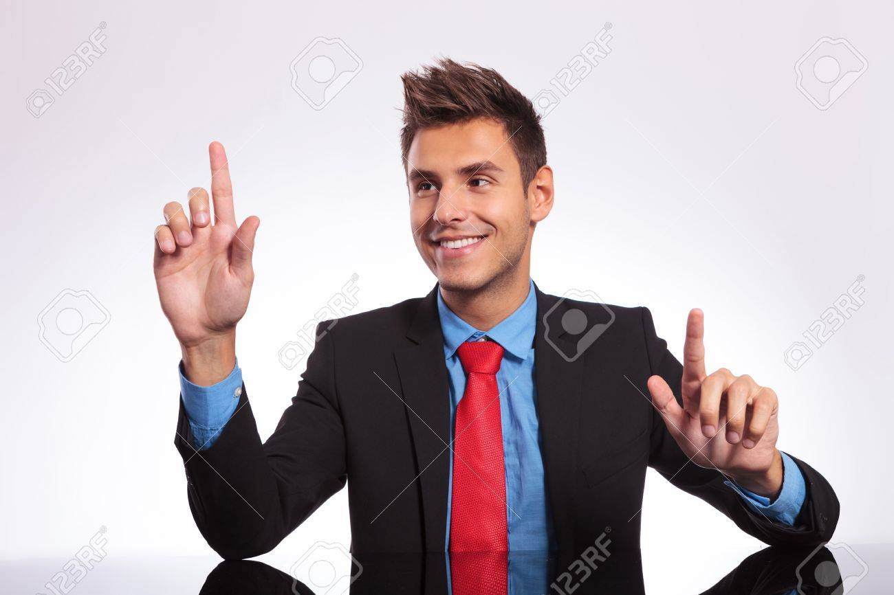 young business man sitting at his desk and pressing two imaginary buttons, with his look at one of them Stock Photo - 18025269