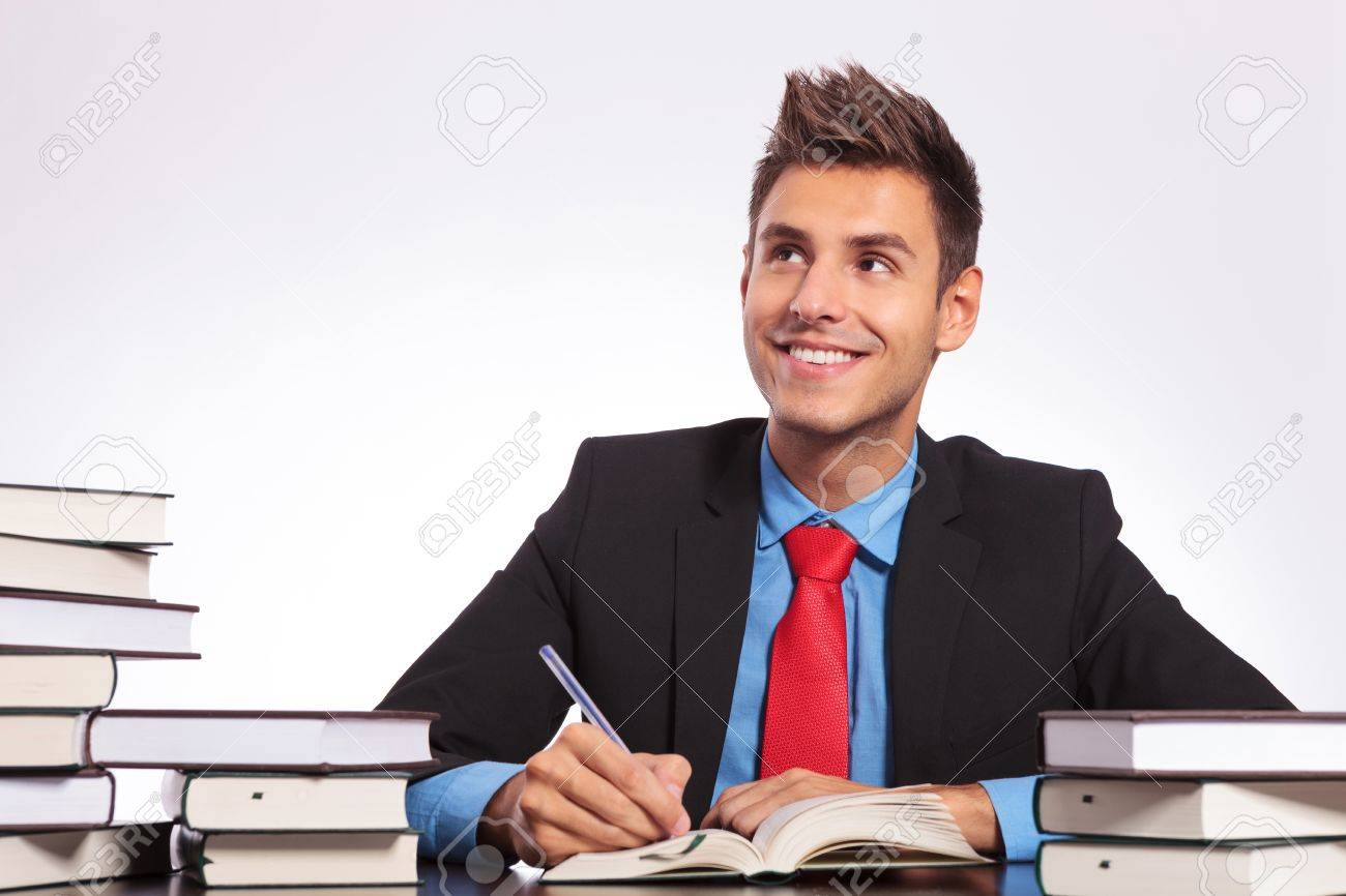young business man at a desk full of books, thinking while witing with a smile on his face Stock Photo - 18025282