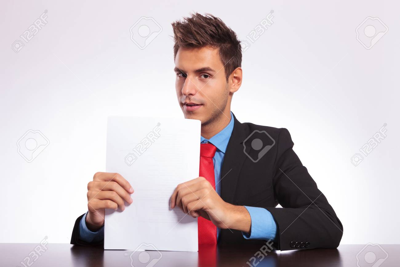 young business man at the table holding some papers and looking into the camera Stock Photo - 18025300