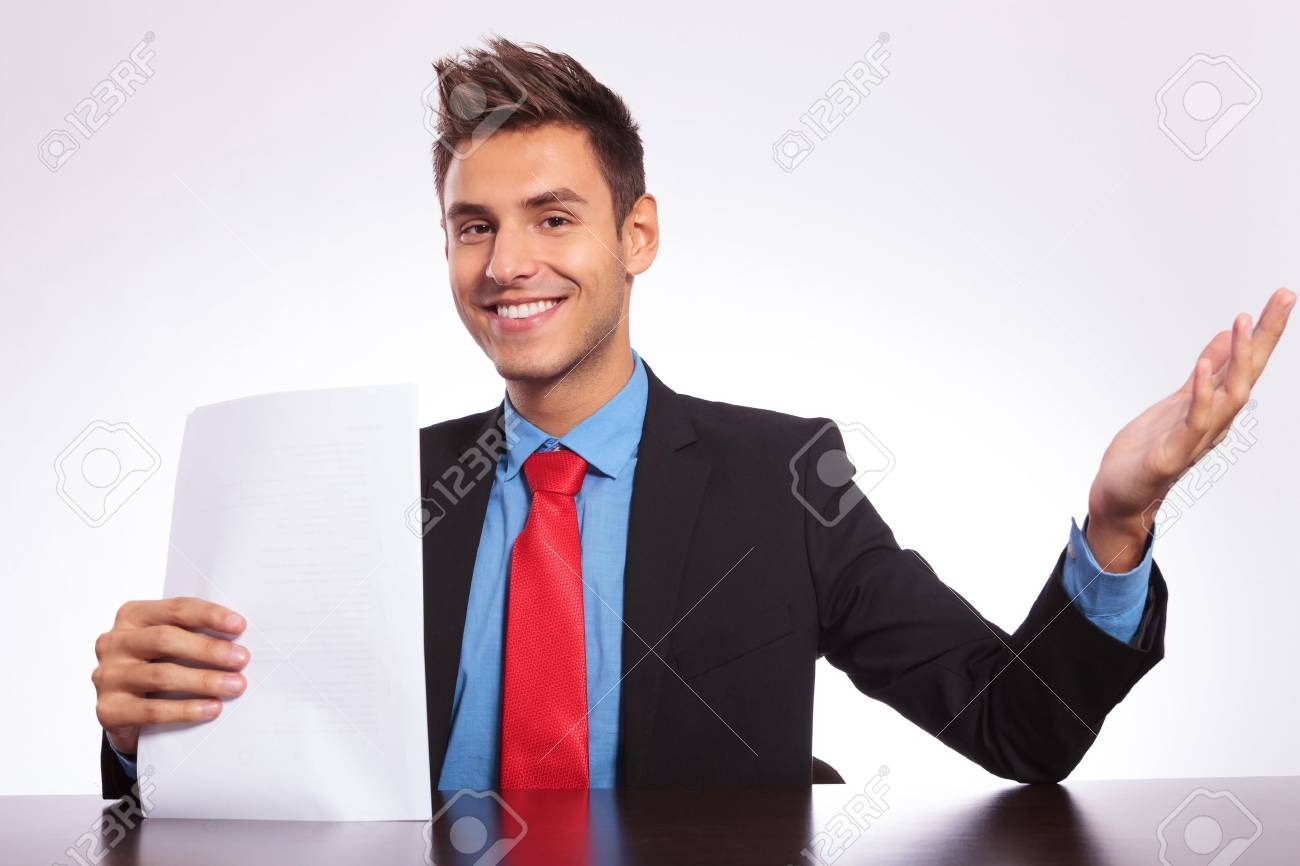 young business man sitting at the desk, holding some paper sheets and making a welcomming gesture Stock Photo - 18025387
