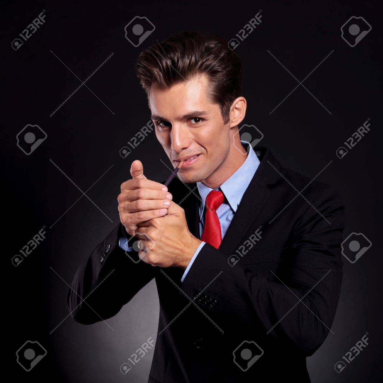 portrait of a young business man standing against a black background and lighting up a cigarette  sc 1 st  123RF Stock Photos & Portrait Of A Young Business Man Standing Against A Black ... azcodes.com