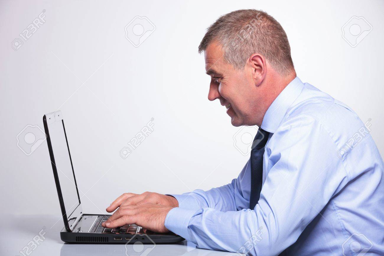 side view of a senior bussines man writing and looking at his laptop. on gray background Stock Photo - 20047754