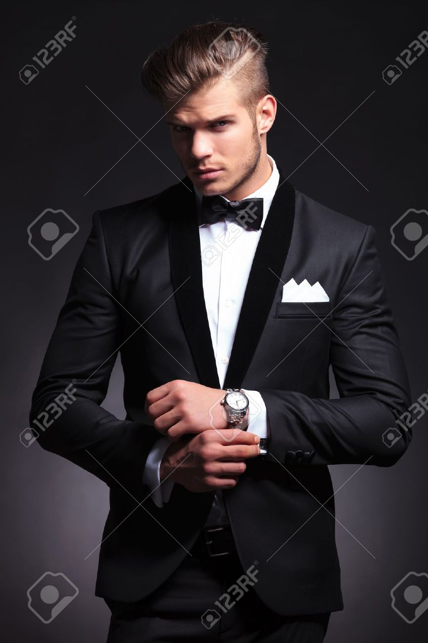 elegant young fashion man in tuxedo adjusting his cufflinks while looking at the camera. on black background Stock Photo - 20482771