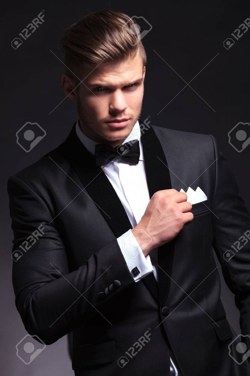 elegant young fashion man in tuxedo holding his pocket handkerchief with a hand while looking at the camera.on black background Stock Photo - 20482690