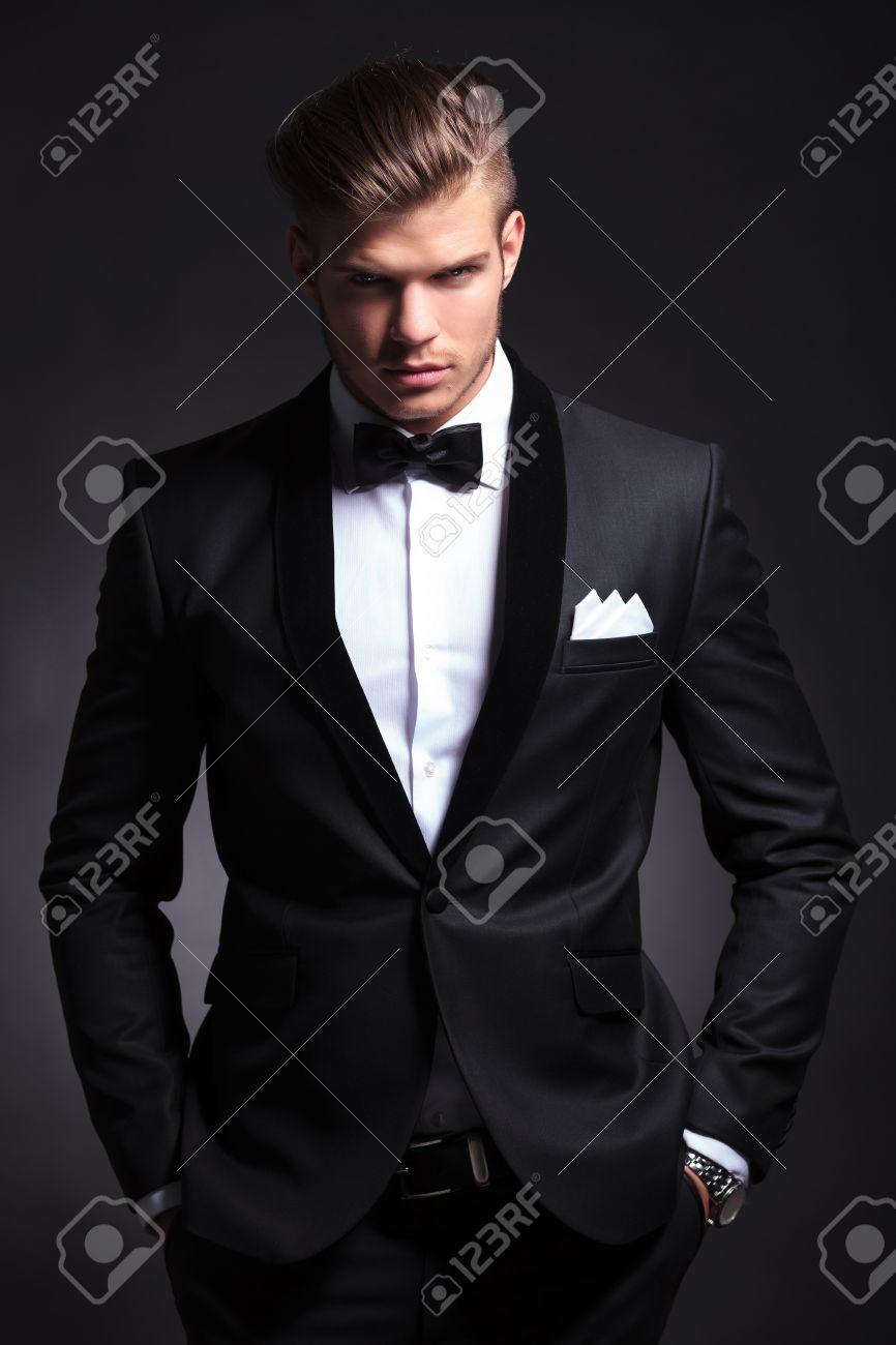 Elegante hombre de moda joven en el smoking es la celebración de ambas manos en los bolsillos y mirando el fondo negro camera.on