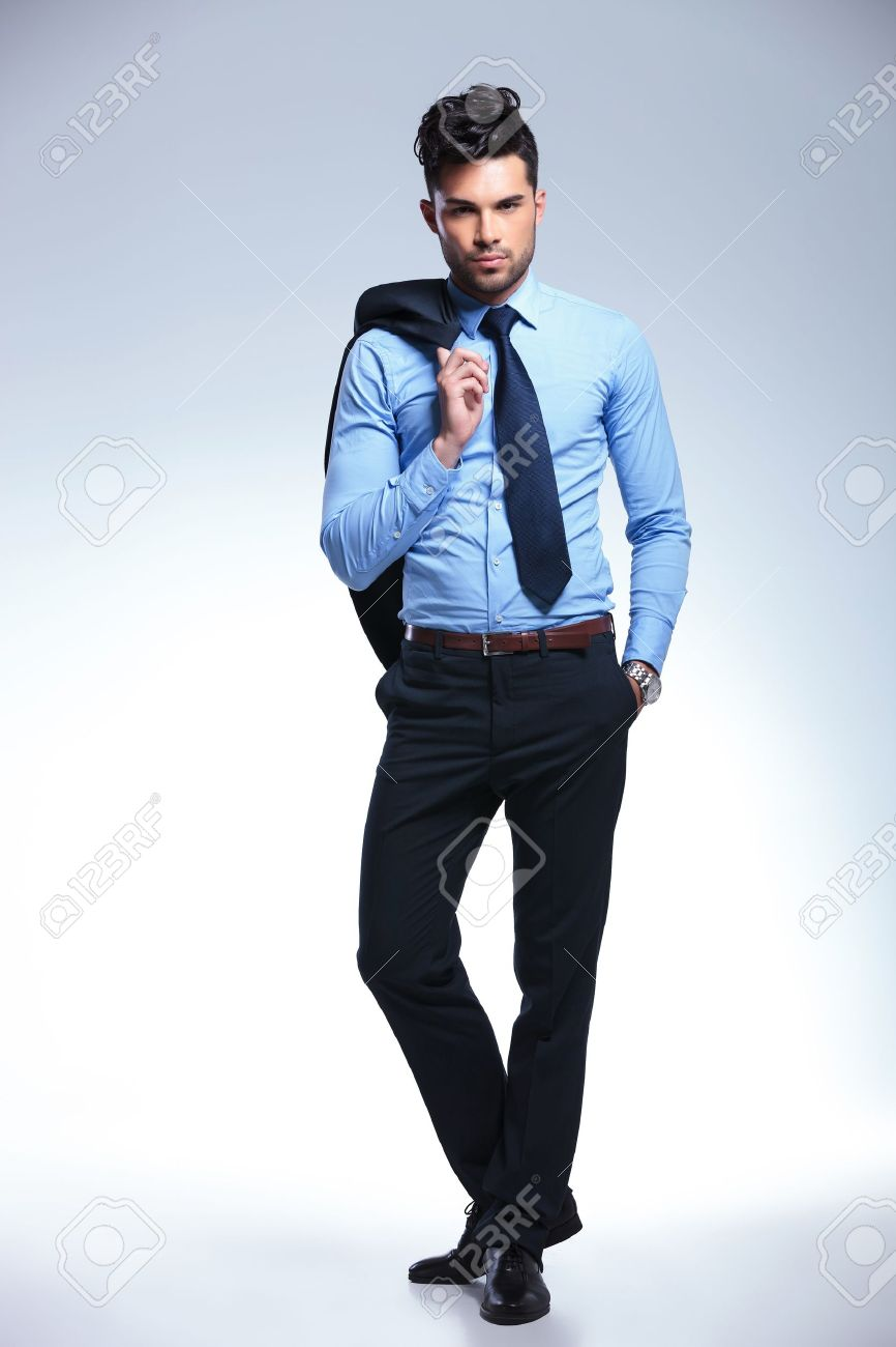 full length picture of a young business man holding his suit jacket on his shoulder and his hand in his pocket while looking at the camera. on a gray background Stock Photo - 20677342