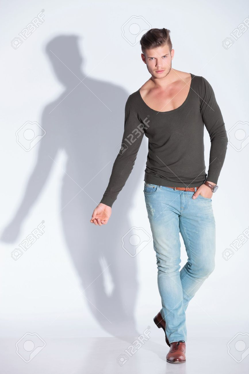 full body picture of a casual young man holding one hand in his pocket while looking at the camera. on gray studio background with shadow Stock Photo - 20999431