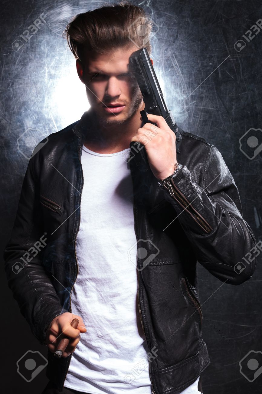 Young Man In Leather Jacket Smoking A Cigar And Holding A Pistol